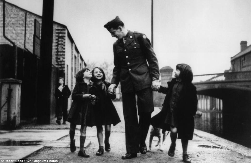 """Soldat américain en compagnie d'orphelins """"adoptés"""" par son unité, Londres, 1943. © Robert Capa"""